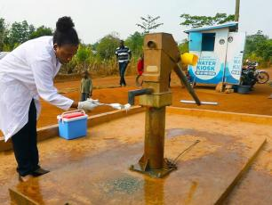 Janet Atebiya purifying the mouth of the pump at Kenyasi, before testing the water for E. coli