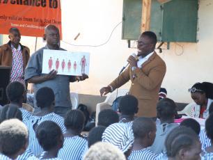 Daniel Karanja telling schoolchildren about menstrual hygiene management