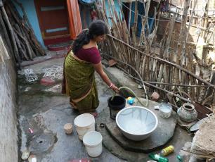 Lady in Odisha filling water vessels