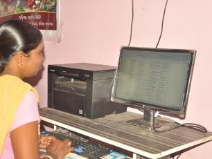 Woman sitting in front of computer screen in Ganjam district, Odisha, India